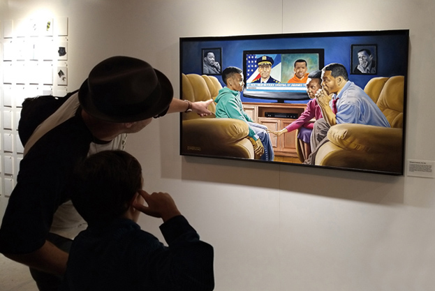 """White father explaining Michael D'Antuono's painting, """"The Talk"""" to his son at the Museum of Broken Windows."""